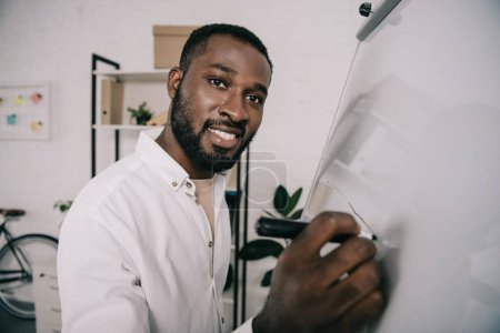 smiling handsome african american businessman drawing on flipchart in office and  looking at camera