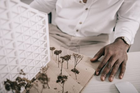 cropped image of african american architect sitting near architecture model on table in office