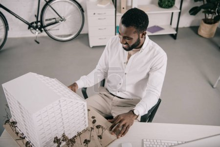 high angle view of cheerful handsome african american architect looking at architecture model in office