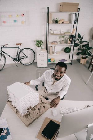 high angle view of smiling handsome african american architect sitting near architecture model and looking at camera in office