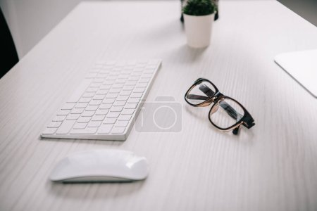 computer keyboard, computer mouse and glasses on white tabletop in business office