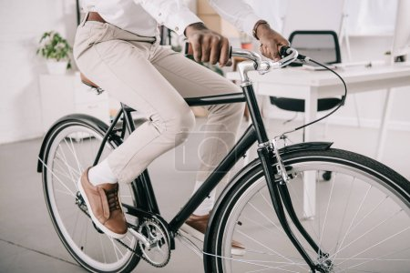 cropped image of african american businessman riding bicycle in office