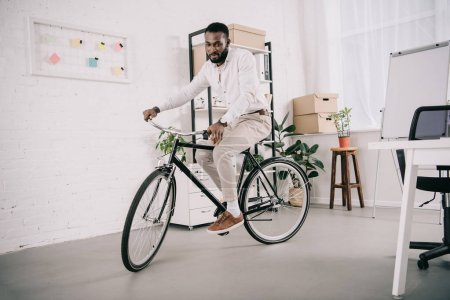handsome african american businessman in white shirt riding bicycle in office