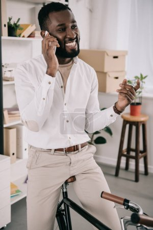 handsome african american businessman sitting on bike and talking by smartphone in office