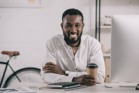 Foto de Sonriendo a apuesto empresario afroamericano con taza de café disponible en la oficina y mirando a cámara - Imagen libre de derechos