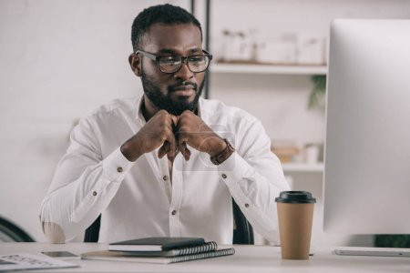 handsome african american businessman looking at computer in office