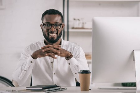 smiling handsome african american businessman sitting at table and looking at camera in office
