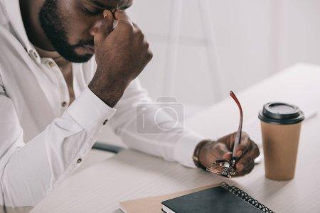 Photo pour Fatigué homme afro-américain toucher pont nasal et verres de tenue dans le Bureau - image libre de droit