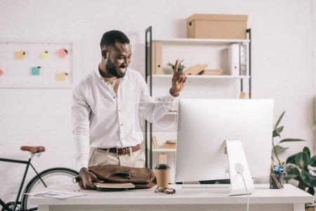 Foto de Empresario americano africano guapo alegre apuntando hacia arriba en la oficina y mirando en el ordenador - Imagen libre de derechos