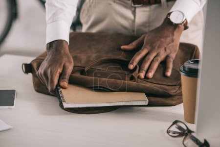 Foto de Imagen recortada del empresario afroamericano toma portátil de cartera en la oficina - Imagen libre de derechos