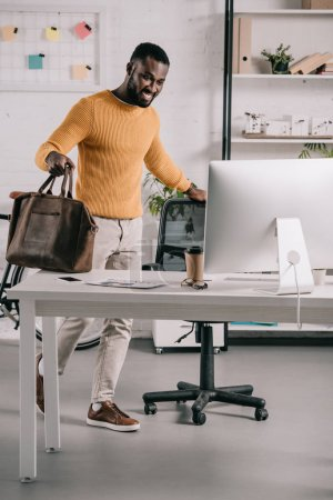 smiling handsome african american designer in orange sweater holding briefcase and looking at computer in office