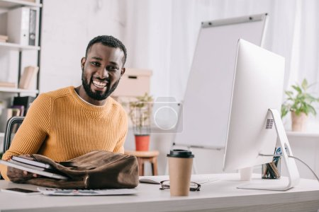 smiling handsome african american designer in orange sweater taking notebooks from briefcase in office