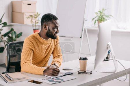 Foto de Diseñador americano africano guapo suéter naranja dibujo en cuaderno y mirando en el ordenador en la oficina - Imagen libre de derechos
