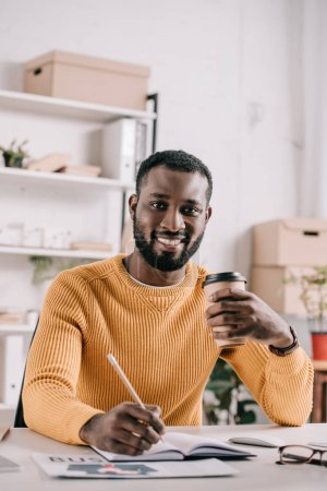 handsome african american designer drawing in notebook and holding coffee in paper cup in office
