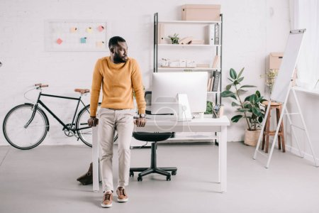 handsome african american designer in orange sweater leaning on table and looking away in office