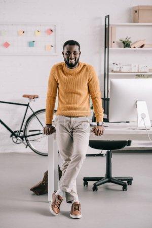 Photo pour Sourire de beau concepteur afro-américaine dans le chandail orange se penchant sur la table et en regardant la caméra dans le Bureau - image libre de droit