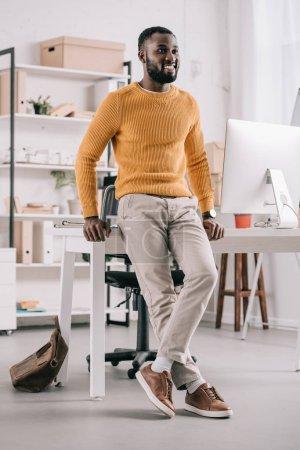 Photo pour Sourire de beau concepteur afro-américaine dans le chandail orange se penchant sur la table et à la recherche de suite au bureau - image libre de droit
