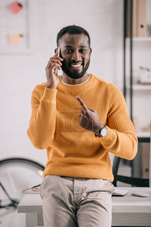 Photo for Cheerful handsome african american designer talking by smartphone and pointing on gadget in office - Royalty Free Image