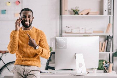 Photo pour Sourire de beau concepteur afro-américaine dans le chandail orange parler de smartphone et pointant sur le gadget de bureau - image libre de droit