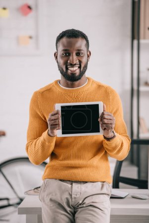 portrait of smiling handsome african american designer in orange sweater showing tablet with blank screen in office