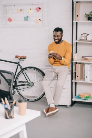 smiling african american designer in yellow sweater using smartphone in office with bicycle