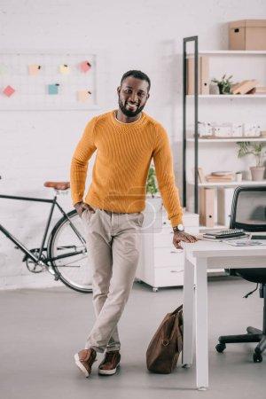 Photo pour Heureux concepteur afro-américaine en due forme pull jaune dans le bureau moderne - image libre de droit