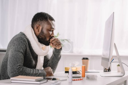 diseased african american businessman coughing at workspace with medicines