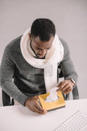 ill african american man taking napkins from box while sitting at workplace
