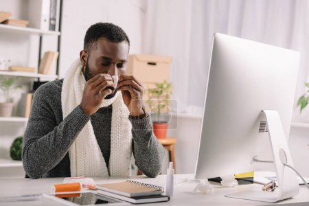 cold african american manager with runny nose holding napkin while sitting at workplace with computer