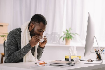 ill african american man with runny nose holding napkin while sitting at workplace with computer and medicines
