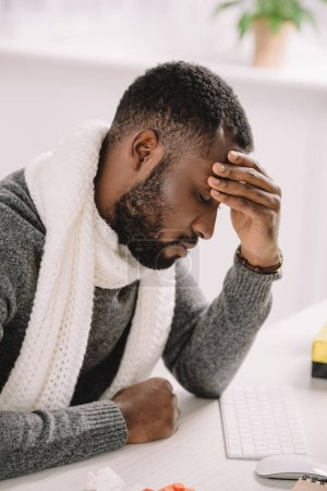Photo for Tired young african american man with headache sitting in office - Royalty Free Image