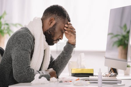 tired african american man with headache sitting in office with treatment and computer
