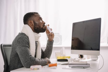 ill african american businessman in warm scarf with nose spray at workplace with computer