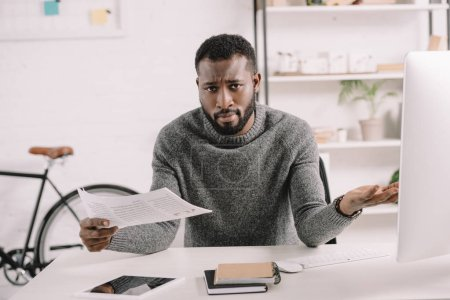 confused bearded african american businessman with shrug gesture holding document in office