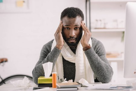ill african american man with headache sitting at workplace with medicines
