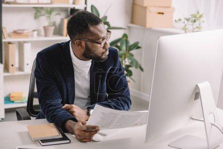bärtiger afrikanisch-amerikanischer Geschäftsmann erledigt Büroarbeit am Computer