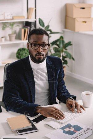 Photo pour Élégant homme d'affaires africain-américain, tapant sur le clavier de l'ordinateur de bureau - image libre de droit