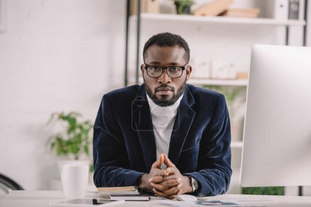 concentrated african american businessman working with computer at workplace