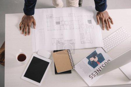 Photo pour Recadrée vue d'architecte travaillant avec blueprint, tablette numérique et journal d'affaires au bureau - image libre de droit