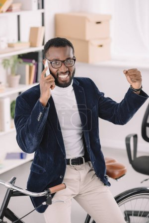 successful african american businessman talking on smartphone while leaning on bicycle in office
