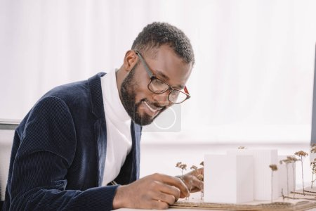 smiling bearded african american engineer working with business buildings model