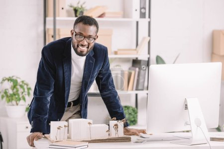 successful african american architect working with business buildings model and computer in modern office