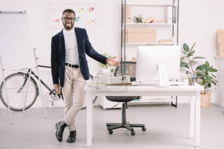 smiling african american architect working with business buildings model in office with computer