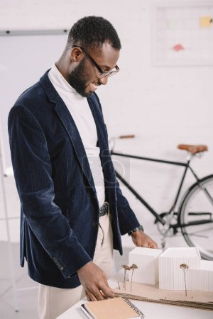 professional cheerful african american architect working with business buildings model in office