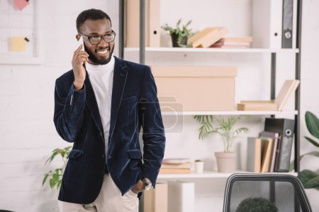 successful african american businessman talking on smartphone in office