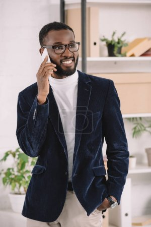 smiling stylish african american businessman talking on smartphone in office