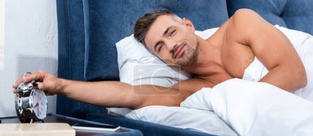 handsome adult man turning off alarm clock during morning time at home