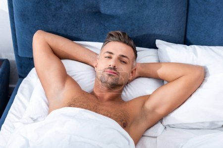 Photo for High angle view of confident adult man laying in bed at home - Royalty Free Image