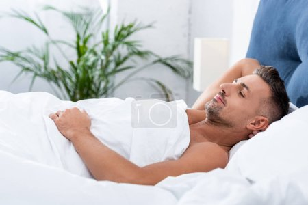 Photo for Side view of cheerful adult man laying in bed at home - Royalty Free Image