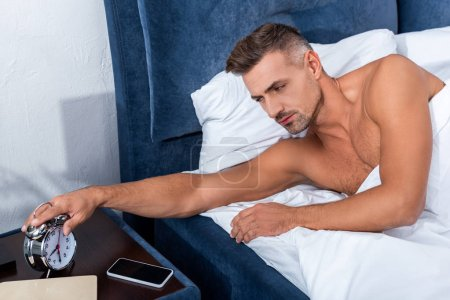 confident adult man turning off alarm clock during morning time at home